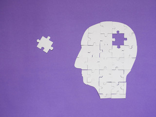 Wall Mural - Head brain white puzzle with missing pieces from jigsaw puzzle on purple background. Creative idea for memory loss, dementia, Alzheimer's disease and mental health concept. Copy space.