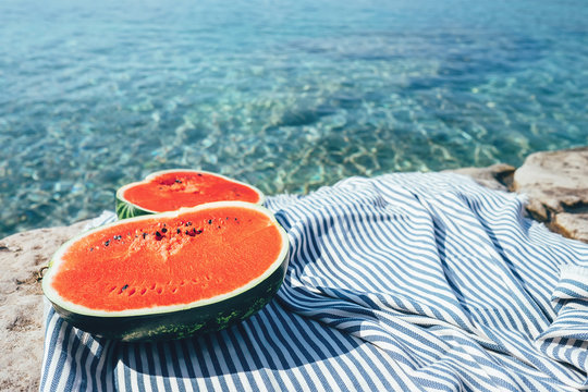 Two big watermelon halfes are on the striped cover near the sea