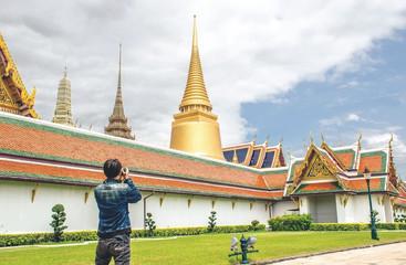 Young Asian traveling backpacker taking photos in Wat Phra Kaew in Bangkok, Thailand