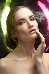 Beautiful elegant girl with a glamorous hairstyle and evening make-up. Portrait on a background of a mirror disco ball, illuminated by green and pink lights.