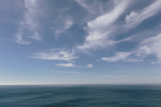 View over the ocean to the horizon, deep blue sea and light windblown wispy clouds in the sky.
