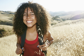 Young woman with curly brown hair hiking in urban park, smiling at camera. Wall mural