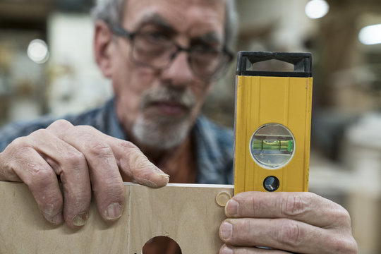 A senior man with glasses and beard in a woodworkers shop, using a spirit level checking his work.