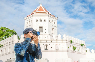 """man traveler with bag cross body and hat and take a photo at """"Phra Sumen Fort"""" background from Bangkok Thailand. Traveling Thailand."""