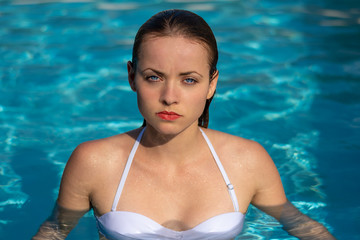 Summertime in pool. Portrait of young sexy woman with wet hair in pool.
