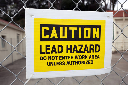 CAUTION LEAD HAZARD sign attached to chain link fence.