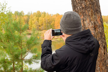 Young man in black jacket and gray knitted hat is taking a photo of autumn landscape on mobile phone in a forest near to the river, back view.