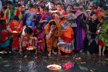 Hindu devotees release oil lamps to the Buriganga river as they observe Bipottarini Puja in Dhaka