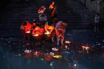 Hindu devotees release oil lamps to the Buriganga river as they observe Bipottarini Puja in Dhaka