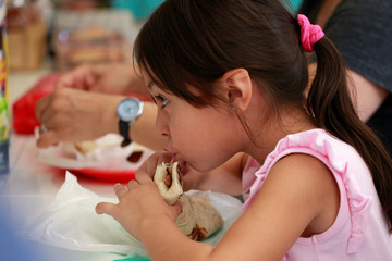 A girl eats a burrito during breakfast at a restaurant in Ciudad Juarez
