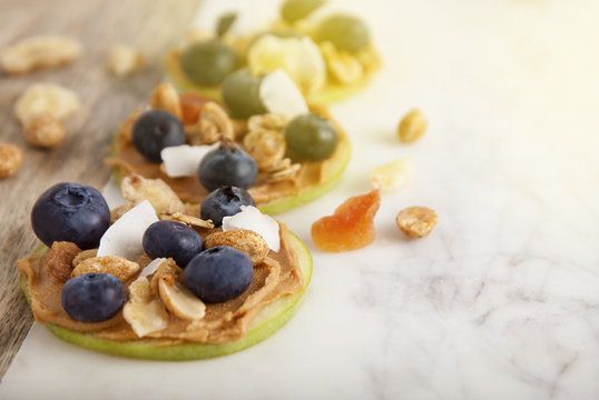 Health and Dieting Food. Green apple slices with peanut butter and blueberries on rustic table Health and Dietting