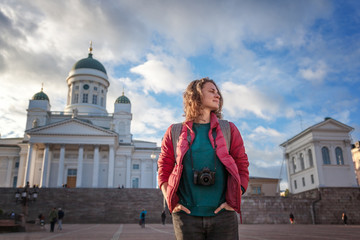 A beautiful young woman traveler with a camera on Senate Square in Helsinki, the capital of Finland, a popular destination for traveling to Northern Europe