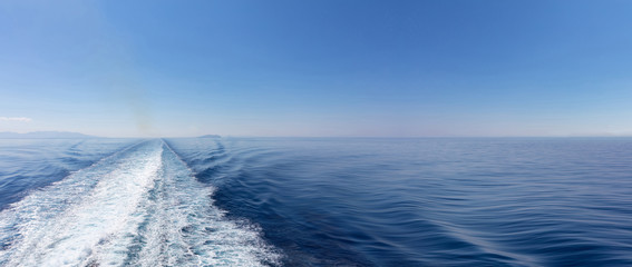 Mediterranean sea. Boat white wake, on blue sea and sky background, view from the ship. Copy space, banner - fototapety na wymiar