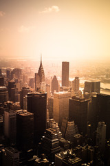 Wall Mural - View of buildings across New York City skyline under golden sunset light