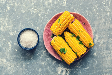 Boiled corn is served with salt on a gray background. View from above.