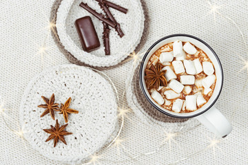 Hot chocolate with marshmallows and chocolate sticks, chocolate candy, star anise on handmade knitted napkin. Holiday concept. Selective focus. Top view.