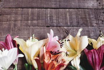beautiful colorful lily flower on rustic wooden background. gorgeous bloom lilies on rustic wood backdrop. space for text. greeting card. celebration concept. spring background, top view.