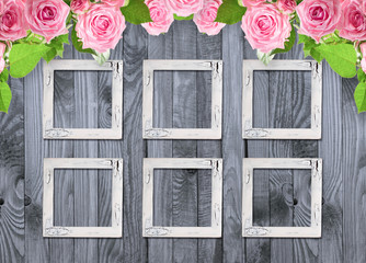 Pink roses and vintage photo frame on wooden background