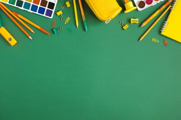School accessories, pencils, paints, pens on green background. Back to school. Flat lay, top view, copy space