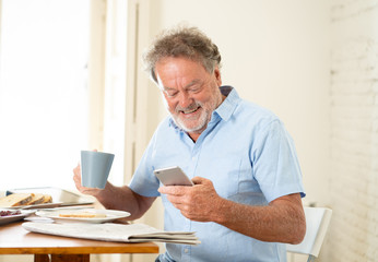 Handsome senior retired old man using mobile phone with joy while having breakfast at home