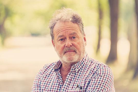 old man looking worried portrait in green park