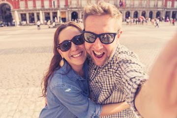 happy couple taking selfie on smart phone in Madrid Spain