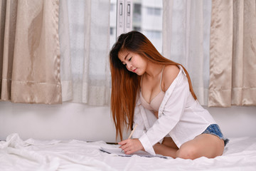 Sexy concept. Young painter are drawing in the bedroom. Beautiful girls are thinking of creating art in the home.