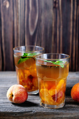 Summer cold drinks: homemade peach sangria with ice cubes, and mint in glass on wooden background