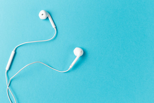 Flat lay concept: headphones on pastel backgrounds. white headphones on a blue background, top view, copyspace. Trendy colorful photo. Minimal style with colorful paper backdrop.