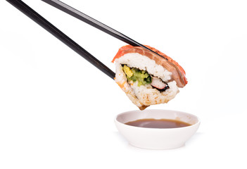 Dipping sushi roll in sauce isolated on white background