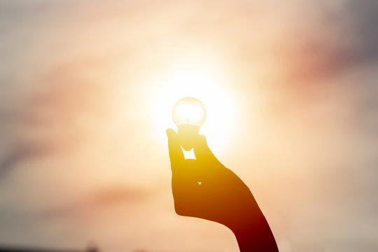 Idea and creativity concept. Silhouette hand holding light bulb with solar energy. New ideas innovation concept. Conceptual solar energy sustainable. Energy savings.