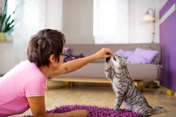 Frau gibt Katze eine Belohnung