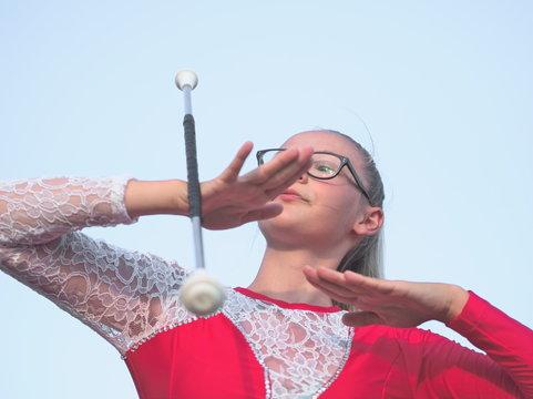 Teen Majorette Girl Twirling Baton Outdoors