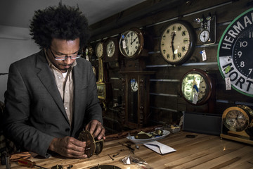 Owner of clock repair shop in New York City working on an old clock
