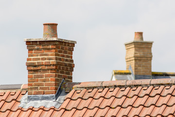 Brick chimney stack on modern contemporary house roof top