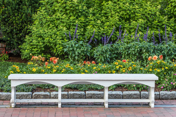 A white bench in a botanical garden