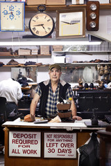 Shoe repair shop owner standing behind counter in New York City, USA