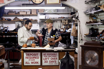 Shoe repair shop owners working behind counter in New York City, USA