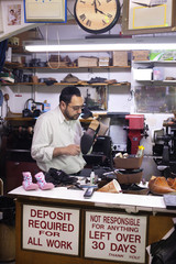 Shoe repair shop owner working behind counter in New York City, USA