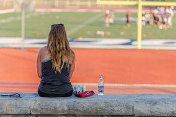 A young lady is sitting on a concrete bench beside a football field