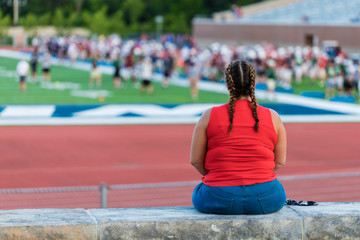 A young lady in red shirt is sitting on a concrete bench beside a football field