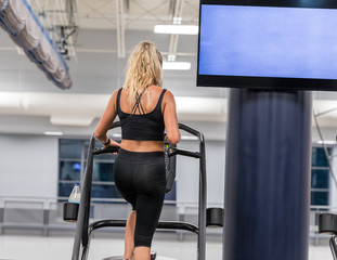 A woman in black sportwear is running on a treadmill