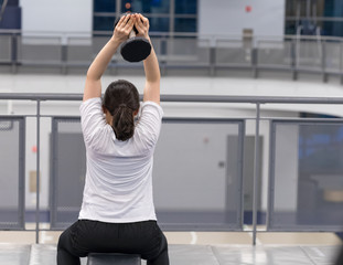 A female athlete stretching with dumbbells