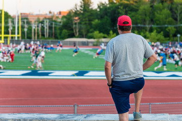 A standing man is watching a football game
