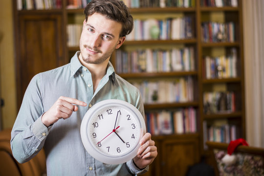 Young casual man holding clock and looking pressed with time limit posing inside at home