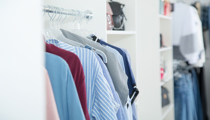 In the women's clothing store. Hanger with a new collection of dresses. Place for text.