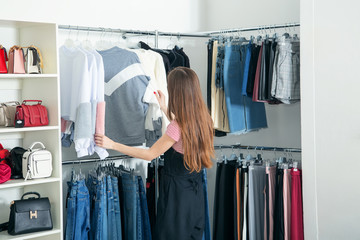 Choose new clothes. A young woman wants to shop at a clothing store.