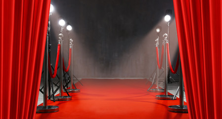 Red carpet, rope barriers and spot lights behind curtains indoors