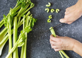 Woman cutting a fresh celery