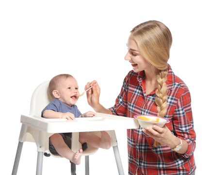 Woman feeding her child in highchair against white background. Healthy baby food